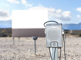 A vintage drive in theater with a close up of the window-mounted speaker.