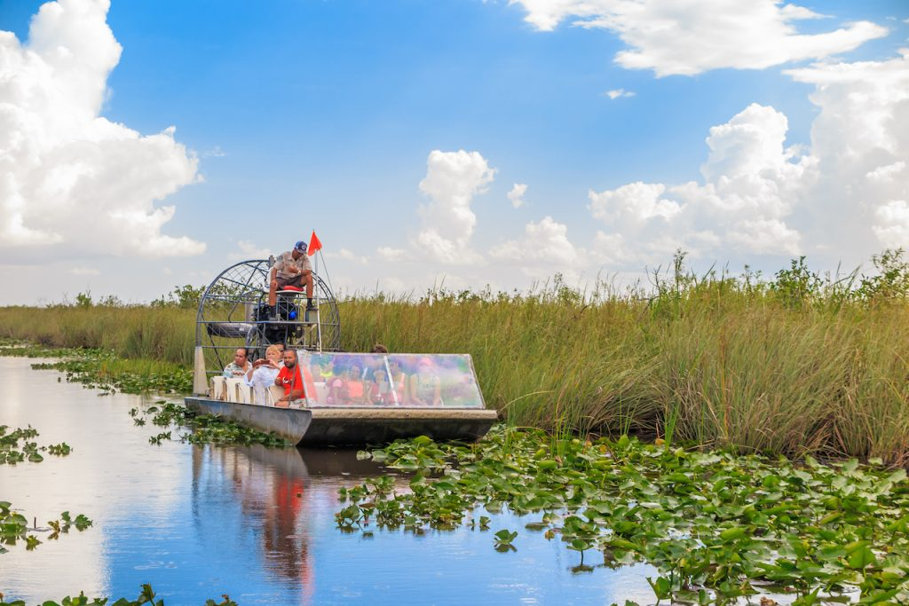 Group of tourists riding an airboat in the Everglades on clear day with white clouds in the sky