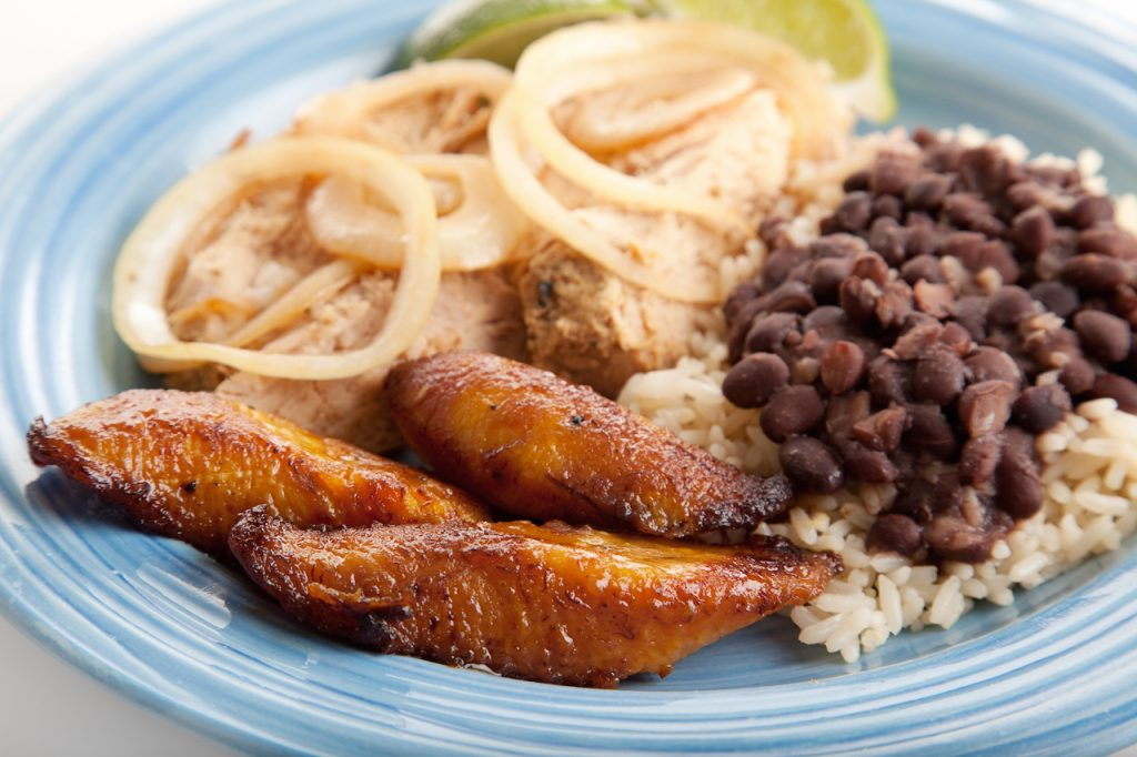 close up of plated cuban food, rice and black beans, plantains, cuban pork
