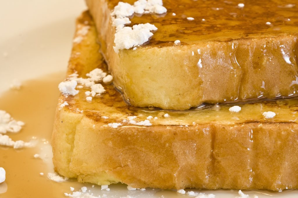 french toast covered with syrup and powdered sugar