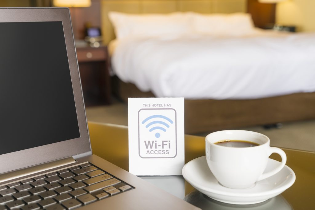 Hotel room with wifi access sign, laptop and cup of coffee