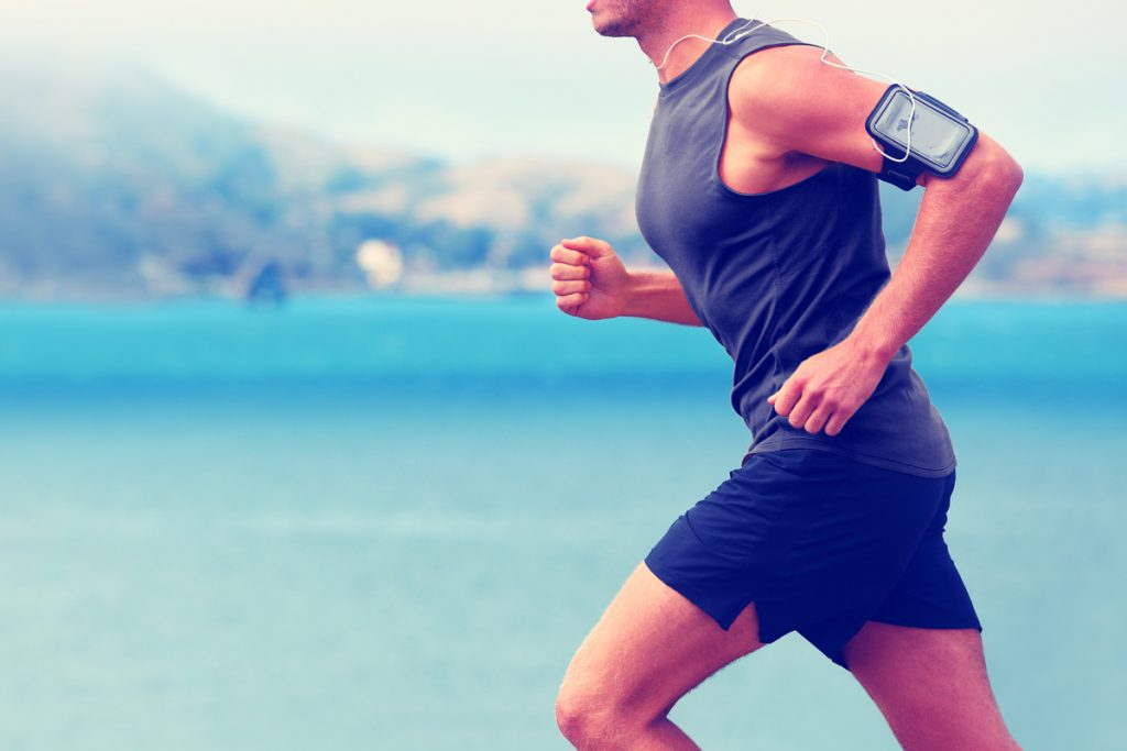 man jogging with a phone strapped to his arm, possibly tracking his fitness