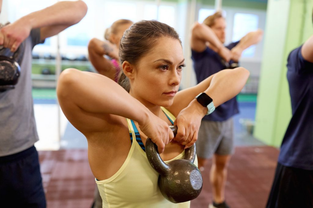 fitness class working out. Picture focused on attractive woman lifting a kettlebell and wearing a fitness tracker watch