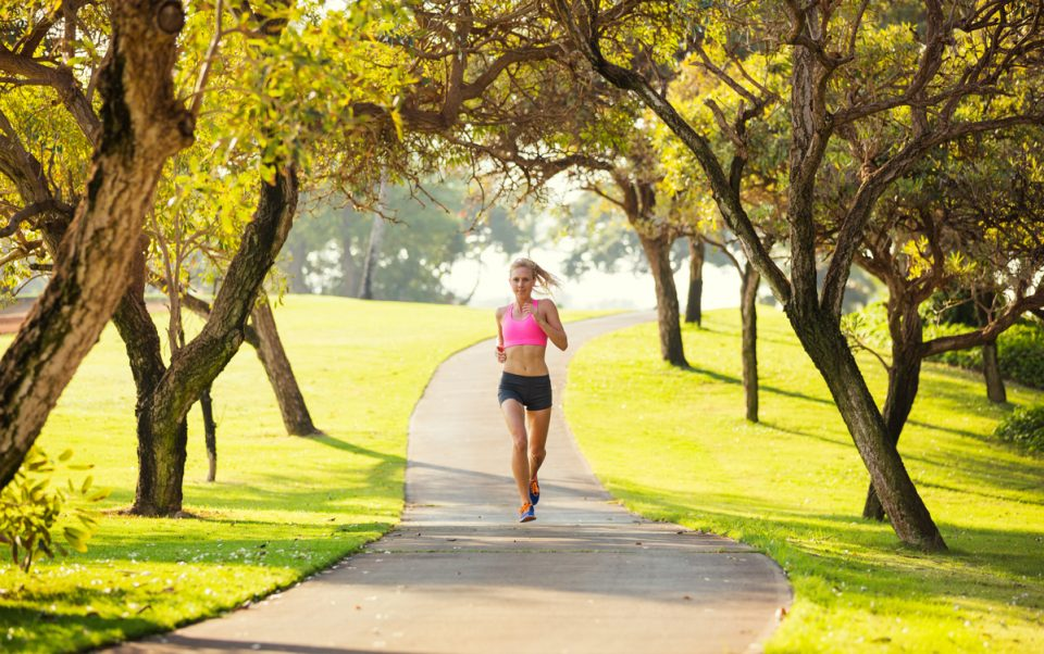 Young woman jogging on Park Trail in the Early Morning