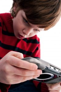 Young boy playing handheld game console, isolated on white background