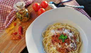 spaghetti in a white bowl on a wooden table with fresh tomatoes and herbs